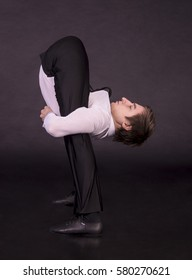 Extraordinary gymnast on a black background. The man with no bones. Studio photography of circus performers