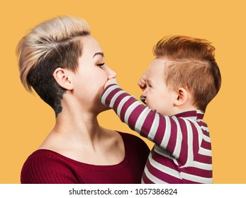 Extraordinary mother with baby boy on hands with hairstyle smiling, isolated on orange. Little baby boy playing with mom and closing her mouth.