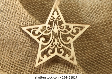 Extraordinary Star Extraordinary intricate wooden five point star with burlap background.