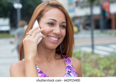 Extraordinary woman with red hair laughing at phone