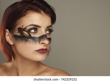 Extravagant girl with cockroaches on her face and bright make up
