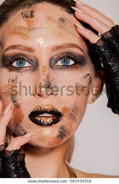 extravagant make-up with gold, black lips and eyes with golden streaks on the face.