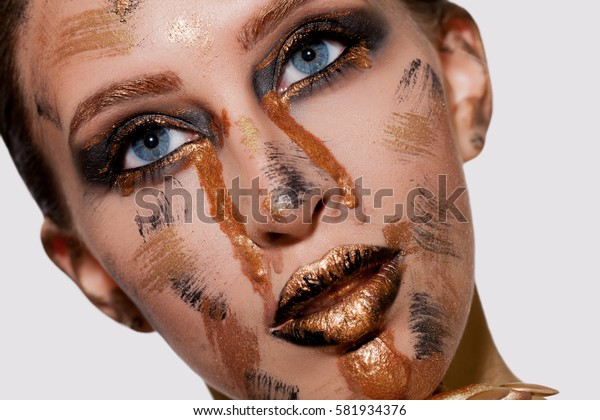 Extravagant Make-up with Gold, Black Lips and Eyes with Golden streaks on the Face