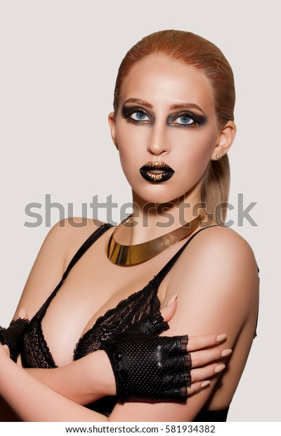 extravagant make-up with gold, black lips and eyes with golden streaks on the face. Portrait of a young woman close-up woman with make-up on her face.