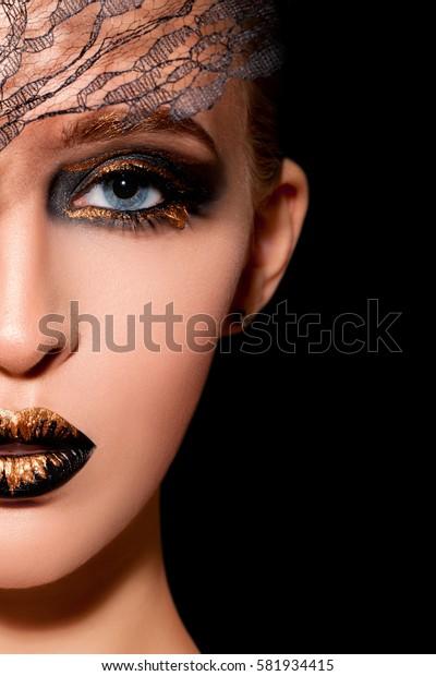 Extravagant make-up with Gold, black lips and eyes with golden streaks on the face. portrait of a girl on a black background