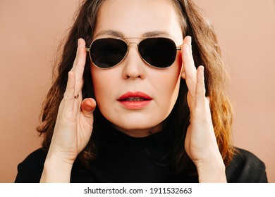 Extravagant middle aged woman fixing her sunglasses, looking at camera. Holding them with palms of her hands. She has bright lipstick, she wears black shirt