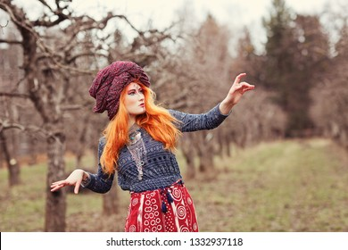 Extravagant redhead young woman wearing ethnic jewelery, clothes and turban with unusual makeup dancing or posing in a mistical forest or park. Psychedelic trance music, yoga, esoterica concept