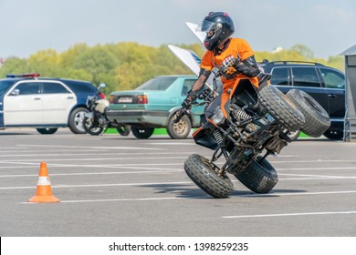 Extreme acrobatics on a Quad bike. A teenage child performs tricks on a Quad bike. The Quad bike is on two wheels sideways. On the back the background of a police car