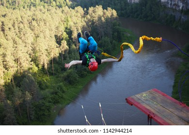Extreme athlete, tied to a safety rope, makes a leap with a coup and falls into a deep canyon from a great height. Ropejumping.