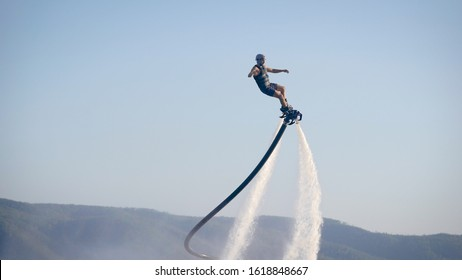 extreme athlete is using flyboard on sea, moving legs and torso to control movements in summer day, view against blue sky