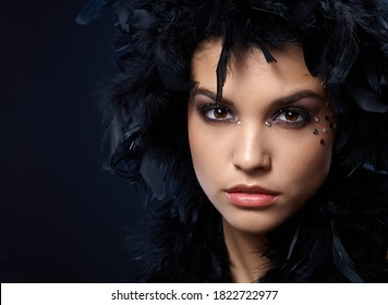 Extreme beauty with rhinestones makeup and wearing black feather boa on head.