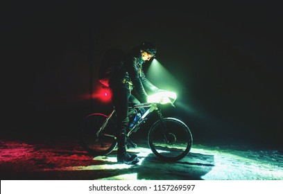 Extreme bike race in winter night. Cyclist on the icy way covered by fresh snow. Cyclist racer in wind and water protective gear. Extreme dangerous sport in the winter outdoors