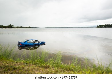 Extreme car crash with drowning car in the lake. Blue vehicle accident with bad end. Traffic incident. Car end in the water after collision with another automobile.