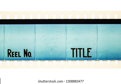 Extreme close up of 35mm movie film strip with reel and title text message on azure