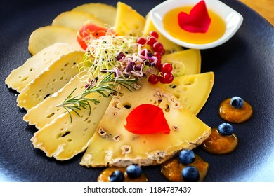 Extreme close up of appetizing cheese platter. Variety of sliced pieces of cheese with fruits and marmalade.