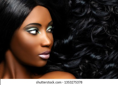 Extreme close up beauty portrait of beautiful young african woman with professional make up. Girl looking aside with long curly hair next to face.
