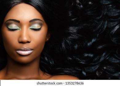 Extreme Nahaufnahme Schönheitsportrait von schöner junger afrikanischer Frau mit professionellem Make-up. Mädchen mit geschlossenen Augen und langen, lockigen Haaren neben dem Gesicht.