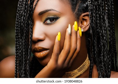 Extreme close up beauty portrait of charming african woman with hand on cheek. Girl with braided hairstyle and sensual look against dark background.