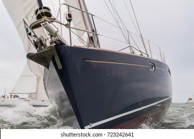 Extreme close up of blue hulled sailing boat, sail boat or yacht at sea with other yachts in the background