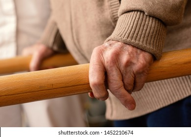 Extreme close up detail of aged human hands grabbing parallel rehabilitation bars.
