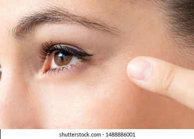 Extreme close up detail of finger pointing at wrinkles around eye on female face.