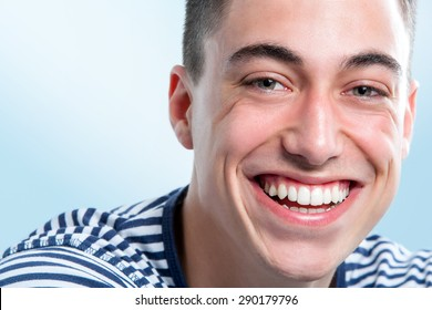 Extreme close up face shot of Young man with charming and healthy toothy smile.