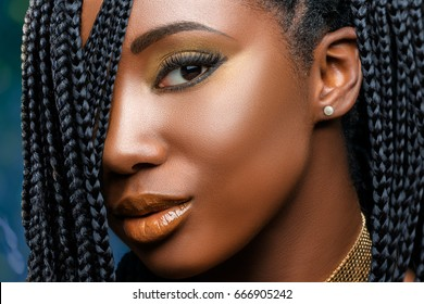 Extreme close up facial beauty portrait of  young charming african girl with braided hairstyle.Studio shot of woman with professional make up looking at camera.