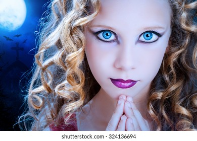 Extreme close up facial portrait of young Girl with big blue eyes. Beauty cosmetic make up on preteen with graveyard at full moon in background.
