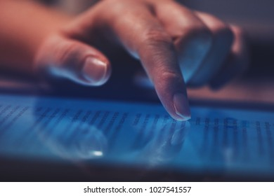 Extreme close up of female finger using digital tablet computer at home in the evening to read the news online, selective focus
