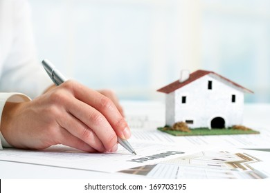 Extreme close up of female hand signing real estate contract.