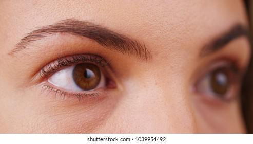 Extreme close up of female millennial's eyes blinking looking off camera
