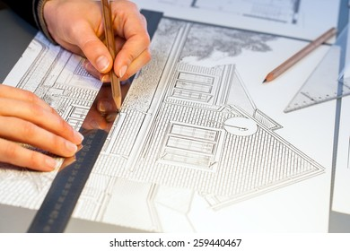 Extreme close up of human hands working on house plan project with pen and ruler.