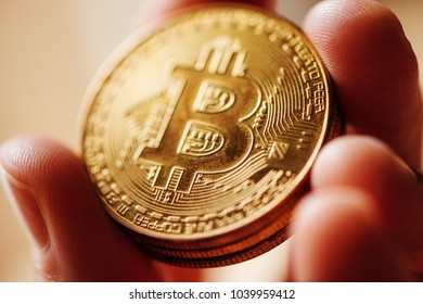 Extreme close up of male hand holding Bitcoin, blockchain cryptocurrency coin, selective focus