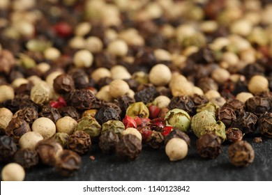 Extreme close up of a mix of black, red, green and white peppercorns on a black, rustic stone kitchen board. Shallow depth of field. Macro food texture background