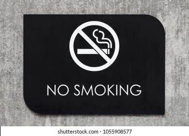 Extreme close up on a black No Smoking sign, with a cigarette symbol in white, on a concrete wall