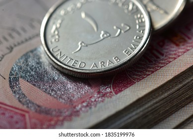 Extreme close up of one Dirham coin placed over hundred dirham note. Currency and coins of UAE.