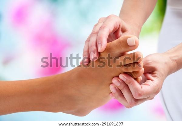 Extreme Nahaufnahme von Physiotherapeuten, die Reflexzonenmassage auf weiblichem Fuß durchführen. Farbiger Hintergrund.