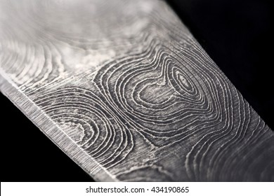 Extreme close up of the raindrop patterning on a damascus steel knife blade, isolated on black.