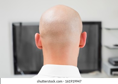 Extreme Close up rear view of a bald man using computer