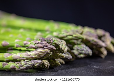 Extreme close up shot of a bunch of green asparagus shoots on a slate plate. Very narrow depth of field.