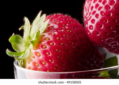 Extreme close up of strawberries in glass on black background