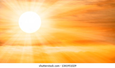 Extreme close up of the sun setting with dramatic golden clouds at sunset and sunbeams. Panoramic image. Shot with pro zoom lens. Peaceful background ideal for religion, freedom, holidays, happiness