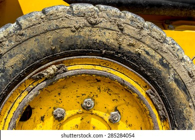 Extreme close up of tire bulldozer, yellow and covered with mud.