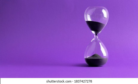 Extreme close up of a transparent hourglass with flowing black sand on blur pink background. Old classic timer. Time concept