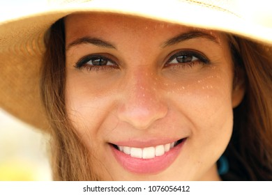 Extreme close up of young model face with straw hat smiling at camera under summer rays sun on the beach. Very close up of photogenic model for tanning or cosmetics cream.