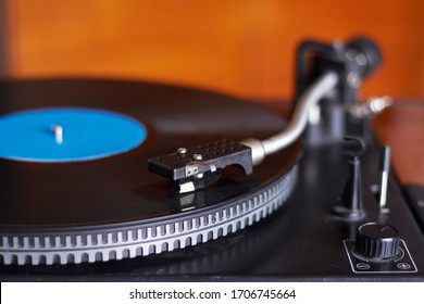 Extreme close-up of blue music record on turntable, turntable needle playing music, selective focus