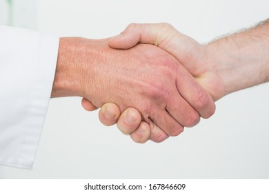 Extreme close-up of a doctor and patient shaking hands in the medical office