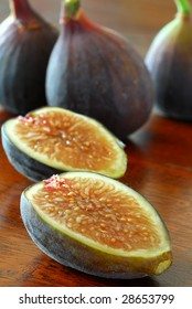 Extreme close-up image of purple figs placed on an old table