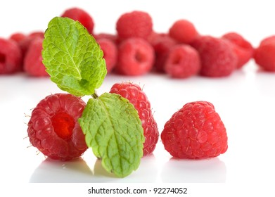 Extreme close-up image of raspberries and mint with more in background