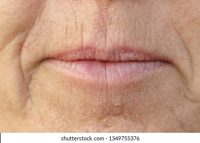 Extreme Closeup on the mouth of a middle-aged brunette woman with her mouth closed and a serious expression